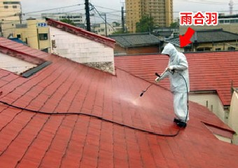 屋根に高圧洗浄を行う作業員
